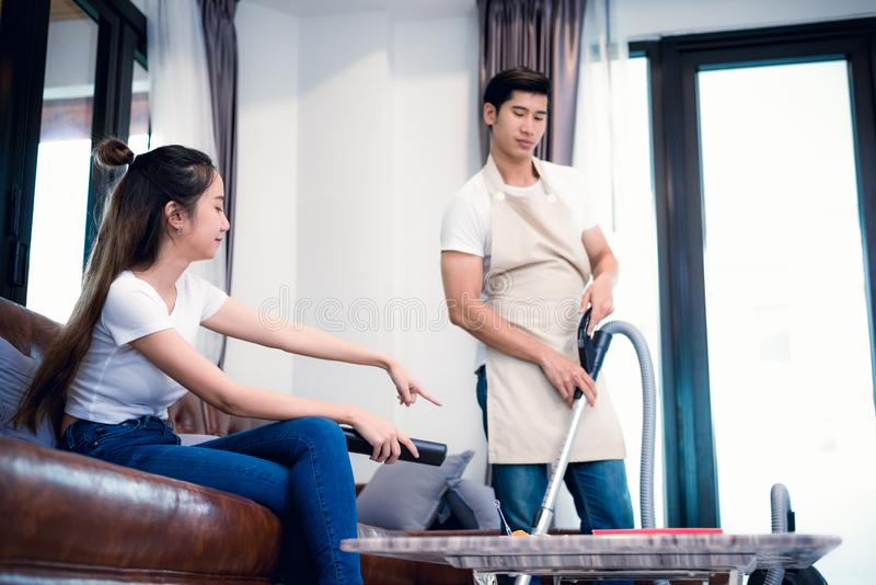 Girlfriend force ordering boyfriend to do household work by vacuum cleaner. Lovers and Couples concept. Honeymoon and Wedding. Theme. Interior and Dating theme royalty free stock images