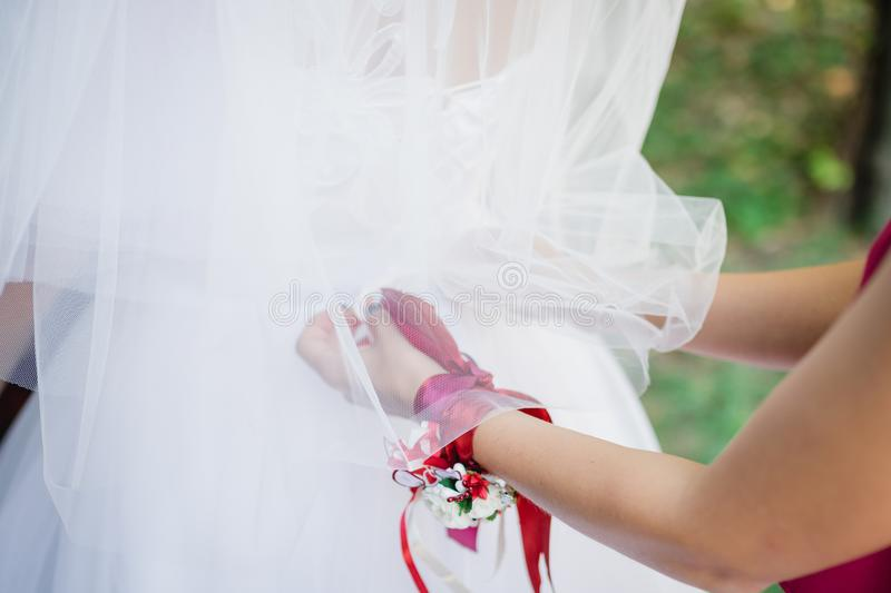 Girlfriend helps the bride get dressed stock photo