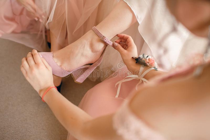 A girlfriend helps a bride to put on her wedding shoes. Beautiful female feet closeup.  stock images