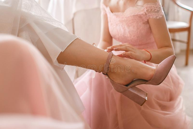 A girlfriend helps a bride to put on her wedding shoes. Beautiful female feet closeup royalty free stock image
