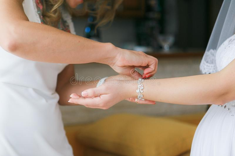 Girlfriend helps to dress the bride a bracelet on a hand befor wedding ceremony stock photography