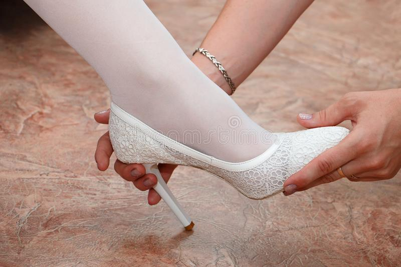 Girlfriend helps to wear wedding shoes. Close up royalty free stock image
