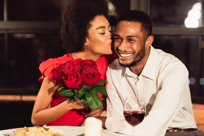 Girlfriend Kissing Boyfriend After Receiving Roses During Date In Restaurant. Happy Love Relationship. African American Girlfriend Kissing Boyfriend After royalty free stock image