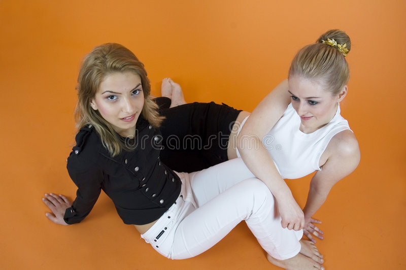 Girlfriends. Two young woman in a comfortable, affectionate pose. Taken in studio with orange background royalty free stock photo