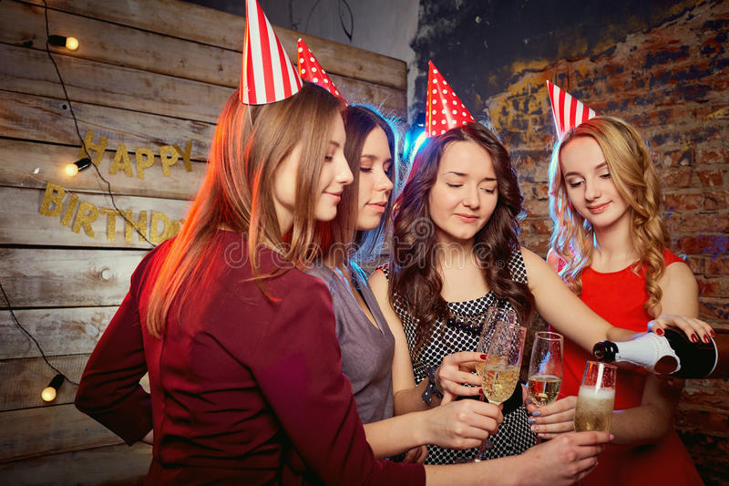 Girlfriends birthday party pour champagne into glasses royalty free stock images