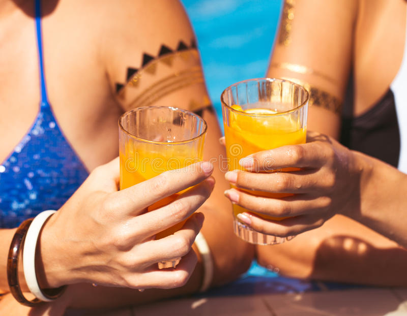 Girlfriends clinking glasses with cocktails at the poolside royalty free stock photos