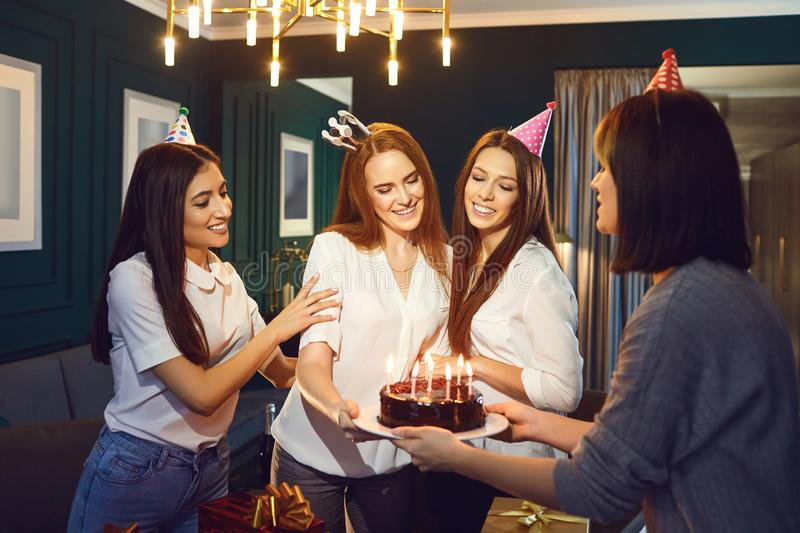 Girlfriends congratulate with cake r a birthday party stock image