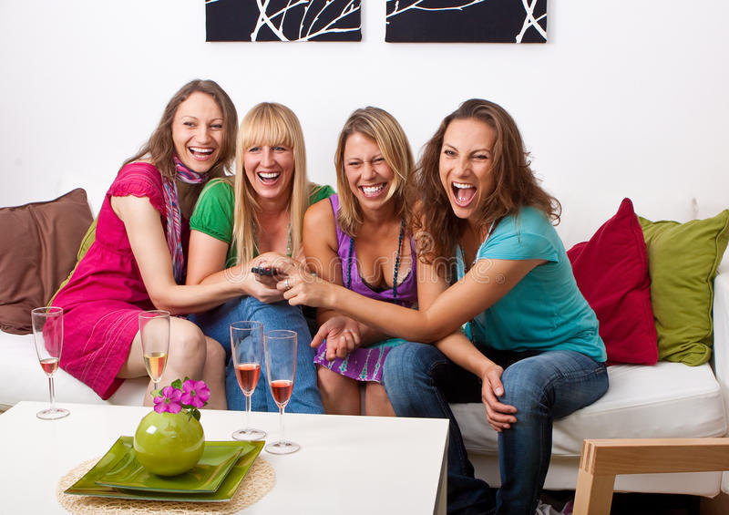 Girlfriends on the couch 1. Pretty girls looking tv and making a little party royalty free stock images