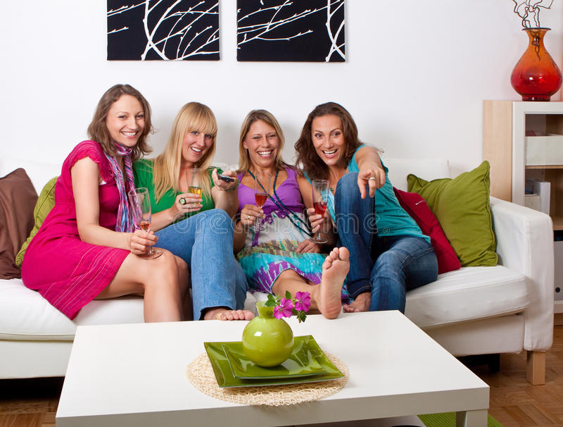 Girlfriends on the couch 3. Pretty girls looking tv and making a little party royalty free stock photography