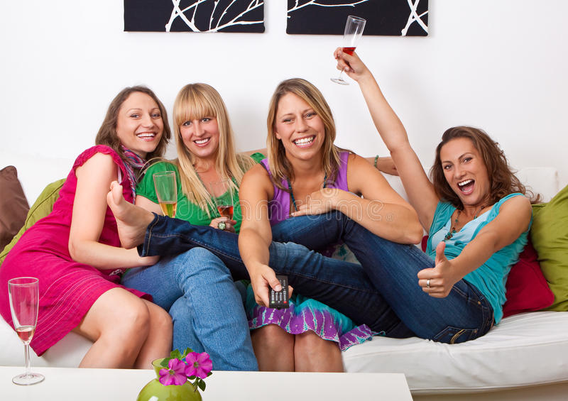 Girlfriends on the couch 4. Pretty girls looking tv and making a little party royalty free stock images
