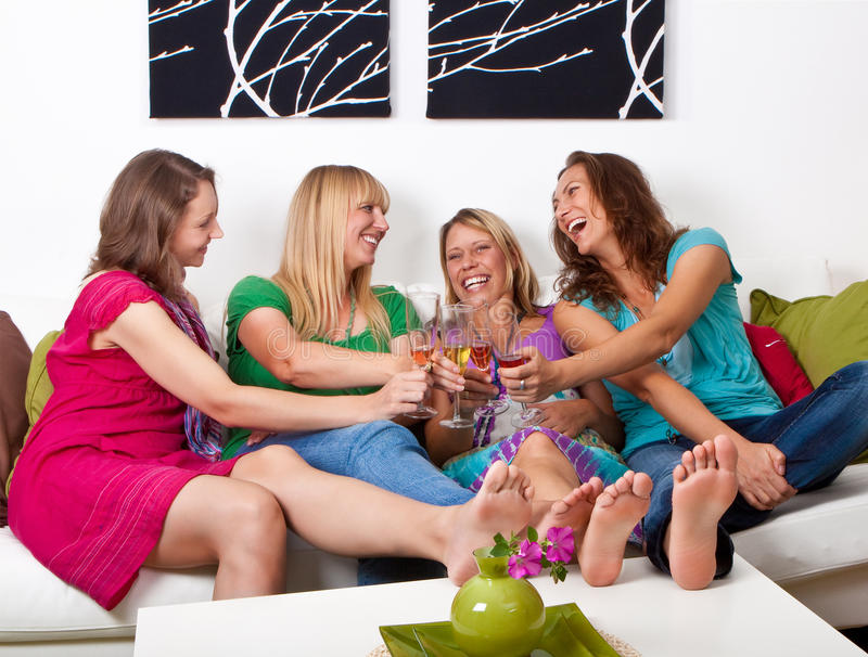 Girlfriends on the couch 5. Pretty girls looking tv and making a little party royalty free stock photo