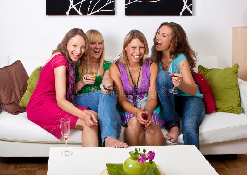 Girlfriends on the couch 6. Pretty girls looking tv and making a little party royalty free stock photo
