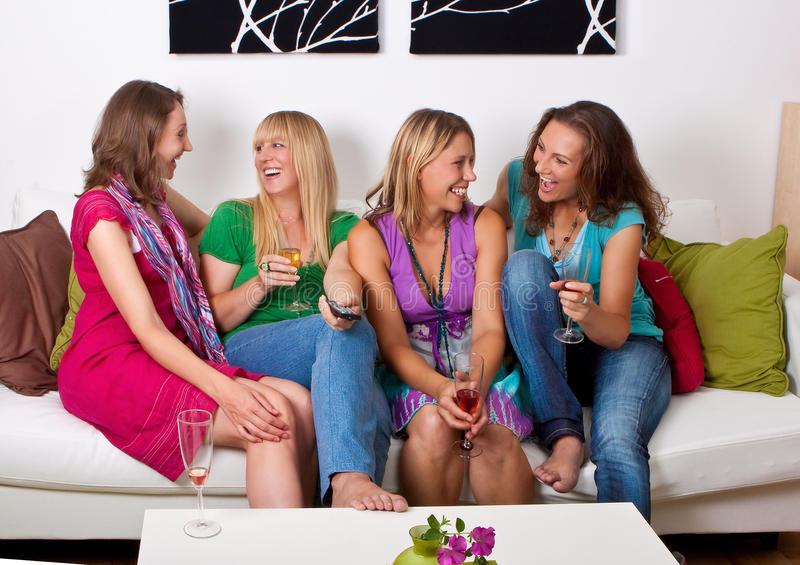 Girlfriends on the couch 7. Pretty girls looking tv and making a little party stock photo