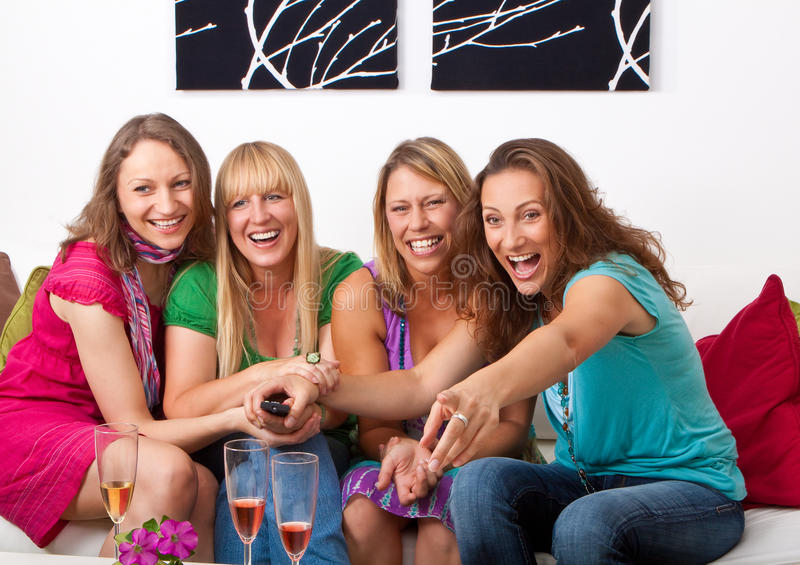 Girlfriends on the couch 8. Pretty girls looking tv and making a little party royalty free stock photos
