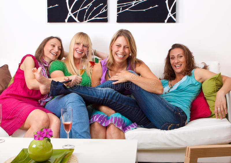 Girlfriends on the couch 9. Pretty girls looking tv and making a little party stock image