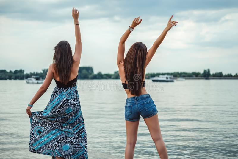 Girlfriends dancing and waving on the beach stock images