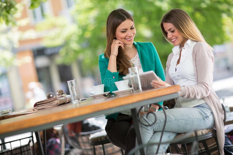 Girlfriends drink coffee and use digital tablet stock photos