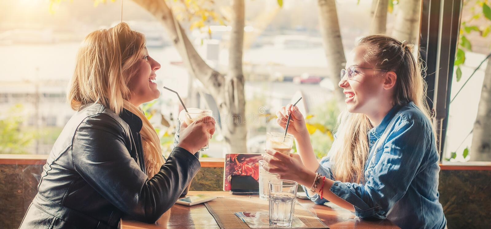Girlfriends having drink at a coffee shop stock photography