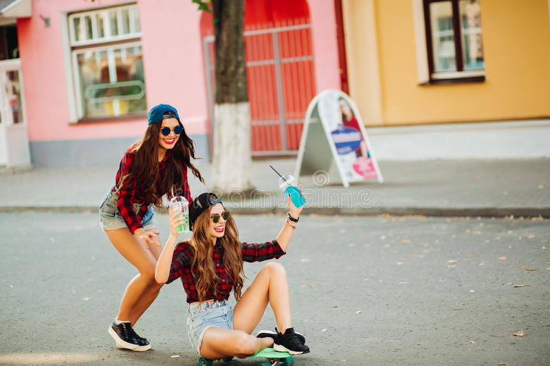 Girlfriends having fun together, riding on skateboard. stock photography