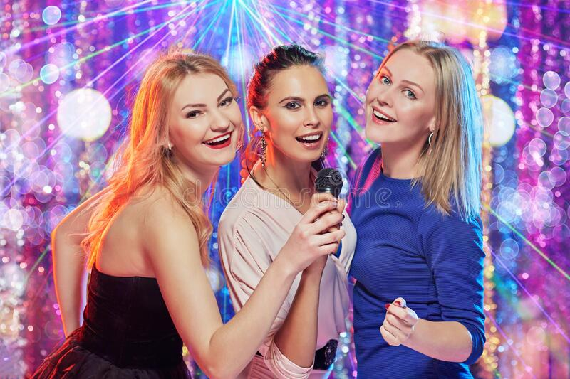 Girlfriends in karaoke club stock photos