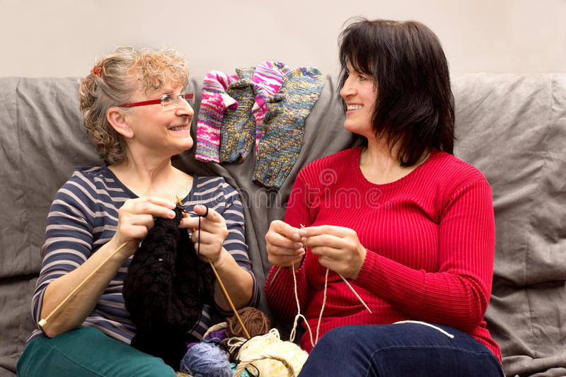 Girlfriends knitting. Two girlfriends knitting together on a couch stock photos