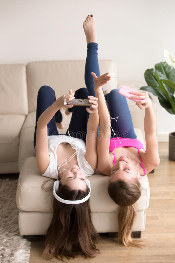 Girlfriends listening music while resting at home. Two young joyful ladies lying on back on couch and listening music with mobile phones in headphones. Relaxed royalty free stock photos
