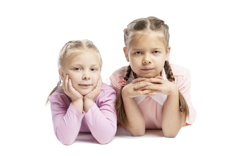 Girlfriends in pink sweaters are lying and smiling. Small children. Isolated over white background royalty free stock images