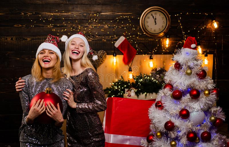 Girlfriends in red Santa hat holding present. Friends Christmas. Christmas and new year concept. Sensual woman. Fashion stock photography
