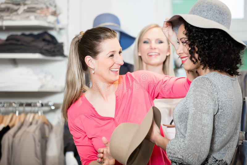 Girlfriends on shopping spree trying ladies hats and other fashi. On items stock photo