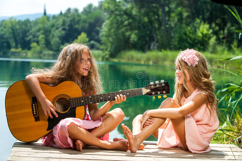 Girlfriends singing together at lake. Portrait of two young girls singing together at lakeside royalty free stock photography