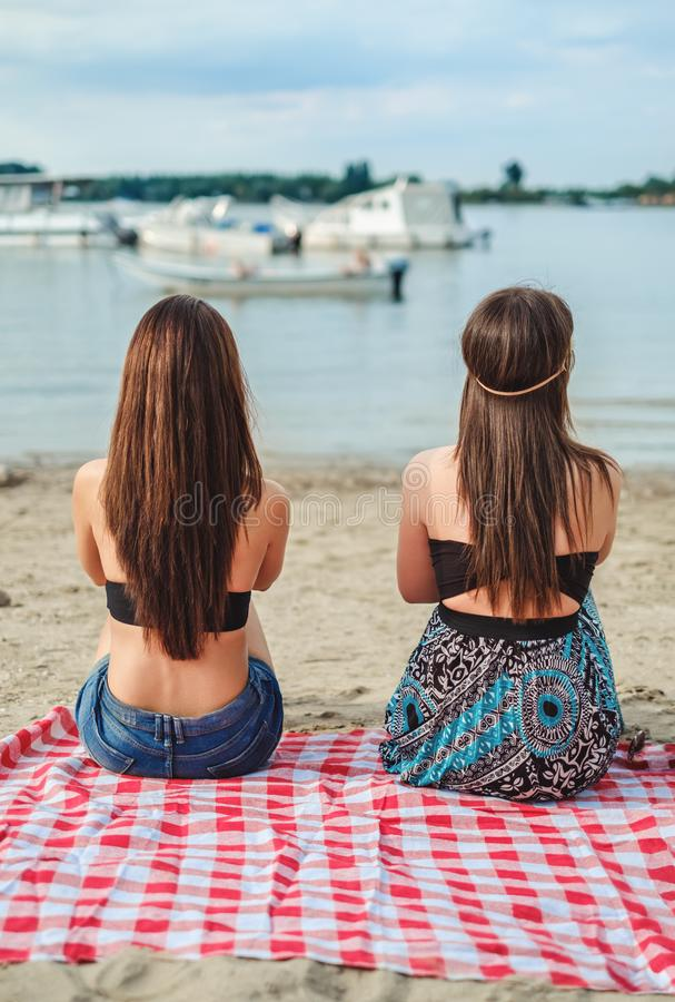Girlfriends sitting on the beach and watching water stock image