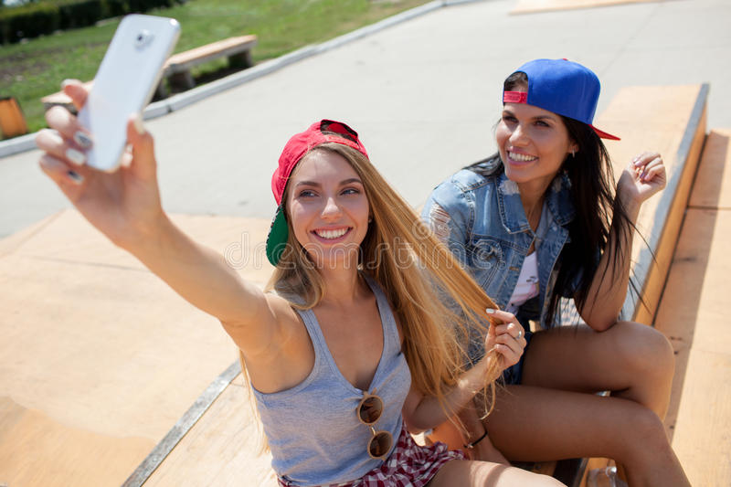 Girlfriends taking a selfie photo on the skate park. Two girlfriends taking a selfie photo on the skate park with smartphone stock photo