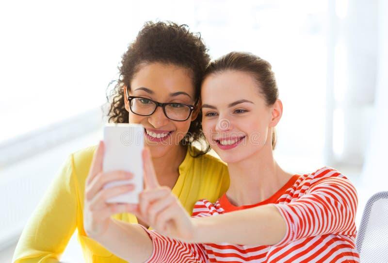 Girlfriends taking selfie with smartphone camera stock photos