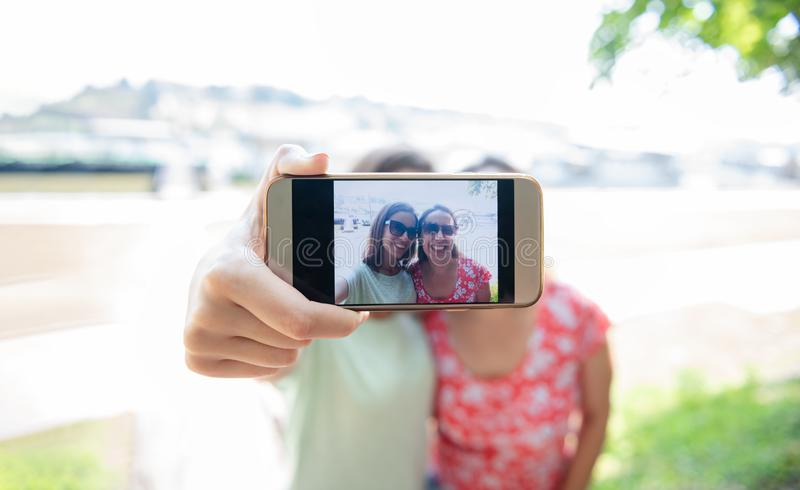 Girlfriends taking selfie together having fun outdoors concept of modern women friendship lifestyle female best friends happy royalty free stock photography