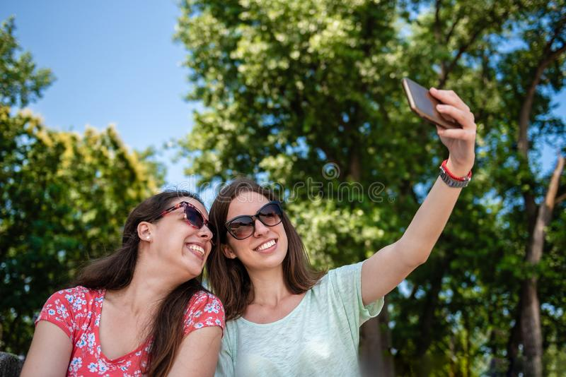 Girlfriends taking selfie together having fun outdoors concept of modern women friendship lifestyle female best friends happy stock image