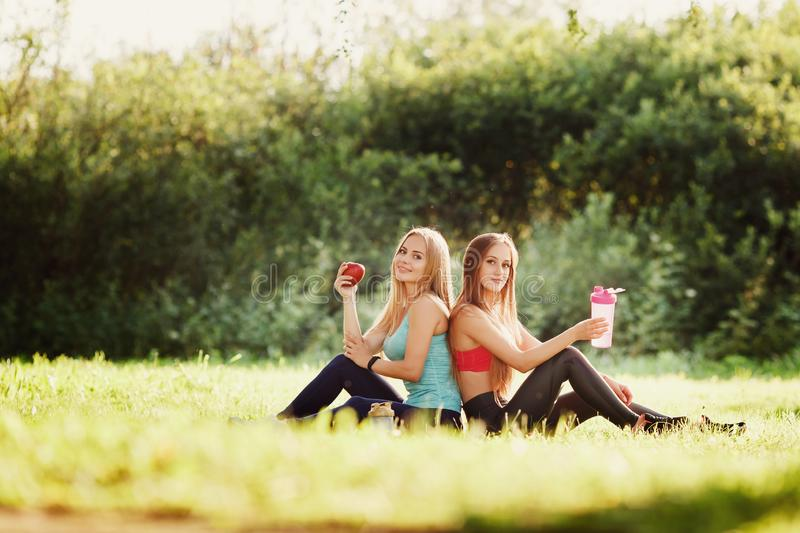 Girlfriends two girls. Are sitting on grass in park holding apple and bottle of water to replenish their strength after training on fitness and yoga stock image