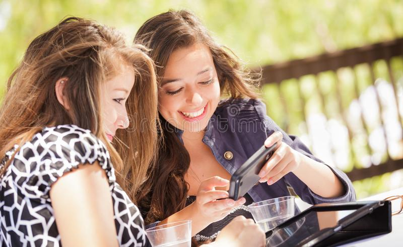 Girlfriends Using Their Computer, Tablet and Smartphone. Expressive Young Adult Girlfriends Using Their Computer Electronics Outdoors stock image