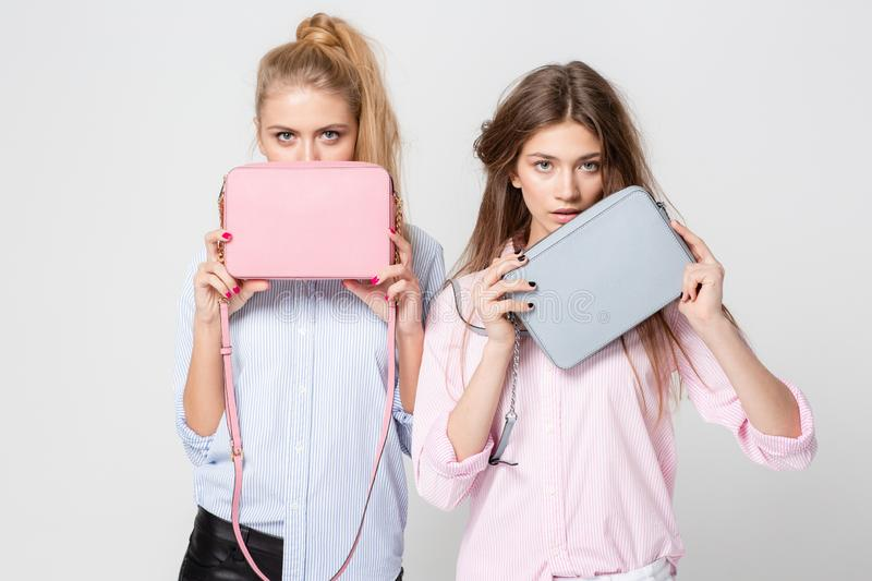 Girlfriends women in shirts with stylish handbags. Fashion spring image of two sisters. Pastel pink and blue colors. Happy girlfriends women in shirts with stock photo