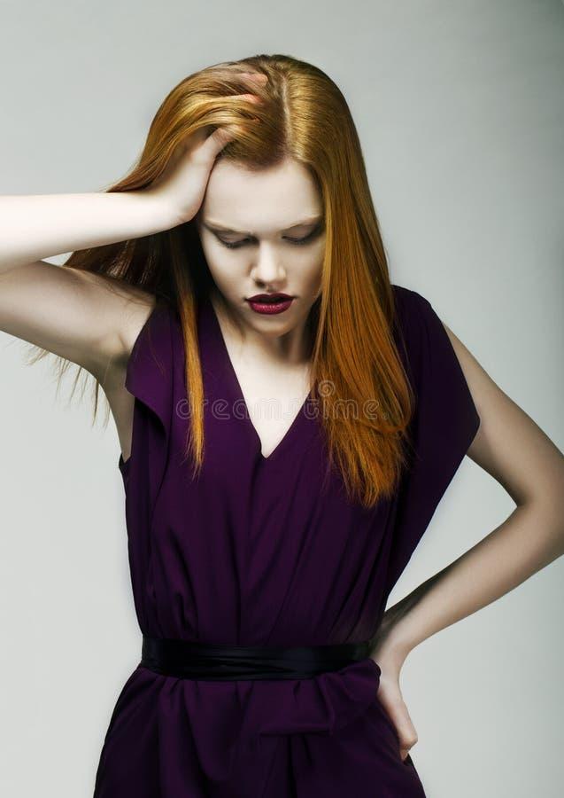 Tristezza. Donna infelice che tiene la sua testa rossa con la mano nello sforzo. Depressione fotografia stock libera da diritti