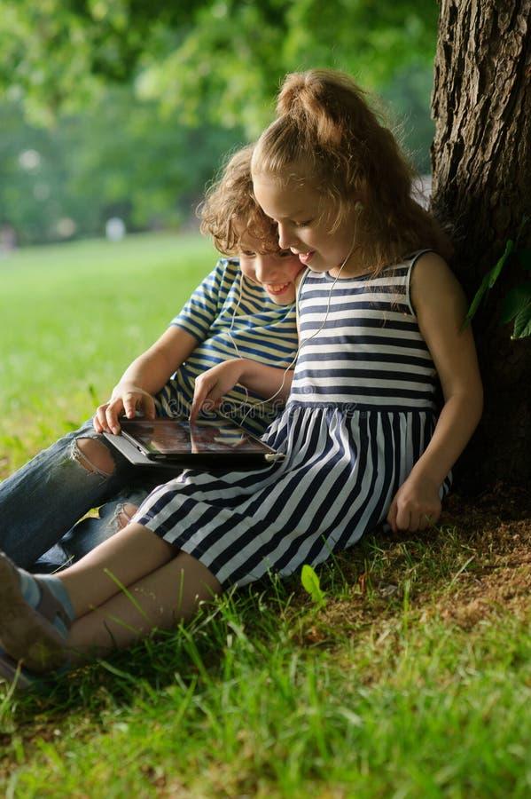 Girlie avec le garçon se reposent sous un arbre s'étant niché et jouent sur le comprimé image stock