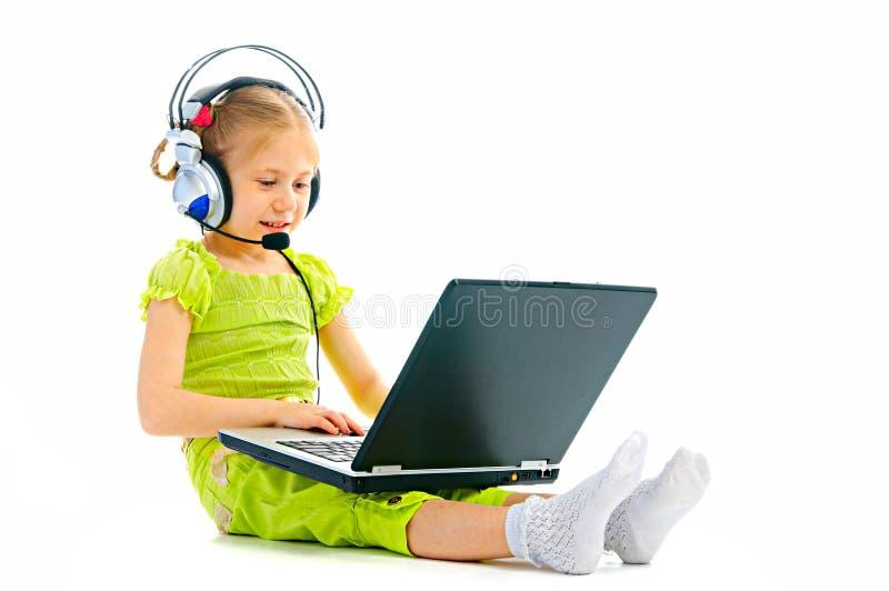 Girlie dans des écouteurs avec l'ordinateur portatif images stock