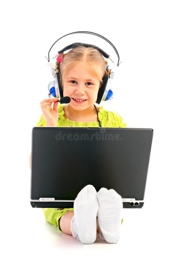 Girlie dans des écouteurs avec l'ordinateur portatif photographie stock
