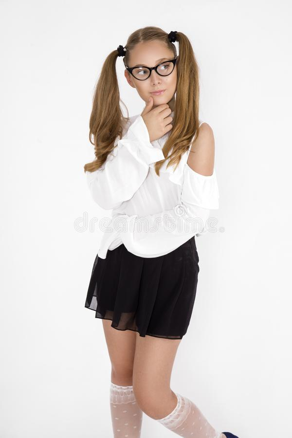 Girlish cute cheerful lovely stylish little girl with curly ponytails in formal blouse shirt, short black skirt. Isolated over royalty free stock photography