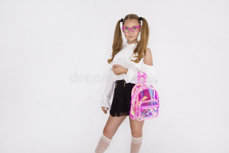 Girlish cute cheerful lovely stylish little girl with curly ponytails in formal blouse shirt, short black skirt. Isolated over stock photos