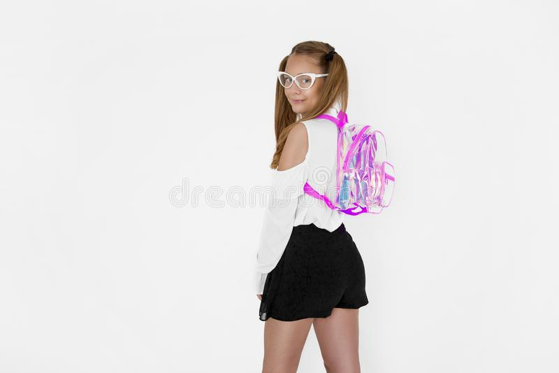 Girlish cute cheerful lovely stylish little girl with curly ponytails in formal blouse shirt, short black skirt. Isolated over royalty free stock image