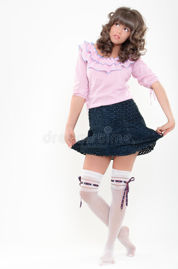 Girlish look. Attractive girl playing with her skirt isolated on white background royalty free stock photos