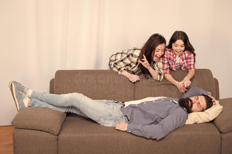 Girlish team. Family prank. Mom and daughter going to cut beard sleeping dad. Lets have fun. Cheerful girls with. Scissors cut long fathers beard. Just for fun royalty free stock image
