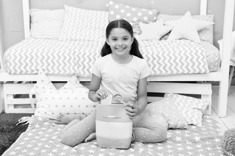 Girlish things. Girl child sit near bed with bag or backpack in her bedroom. Kid prepare to go to bed. Girl kid long. Hair cute pajamas relaxing in bedroom stock photography