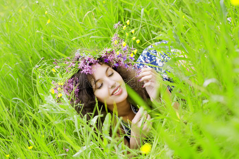 Girll, lying on the grass field. The image of a beautiful girl, lying on the grass field royalty free stock images