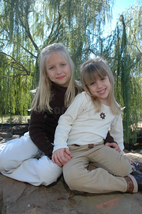 Girls. Two beautiful little blond sisters sit together under a weeping willow tree at a park and spend time together. Sisters are best friends stock photography